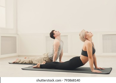 Fitness, man and woman training yoga in cobra pose at home. Young couple makes exercise, copy space