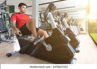 Fitness man working out on exercise bike for cardio workout  male exercising on bicycle at the gym in morning,