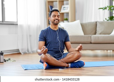 fitness, meditation and healthy lifestyle concept - indian man in earphones listening to music on smartphone and meditating in lotus pose at home