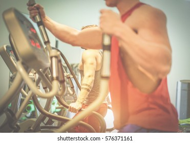 Fitness men using eliptical cross trainer in gym american club - Young athletes running on tapis roulant - Wellness and body building concept - Focus on behind man hand - Warm filter