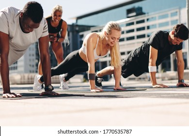 Fitness men and women doing push-ups with motivation from their female trainer outdoors in the city.