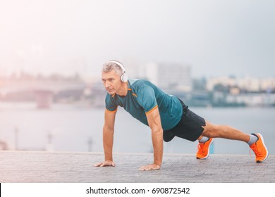 Fitness middle aged man doing push-ups on the riverside. Male athlete exercising outdoors. Sports and active lifestyle.