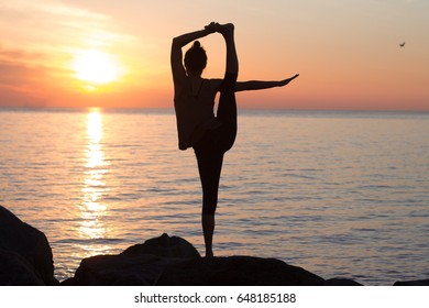 fitness mixed race woman silhouette in yoga pose on the morning beach, beautiful fit woman practice fitness exrxise stones, morning sea or ocean background