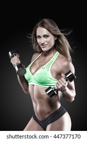 Fitness model with dumbbells on grey background