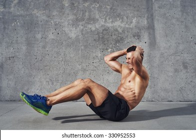 Fitness model exercising sit ups and crunches. Muscular well build, toned body with six pack sweating. Copy space