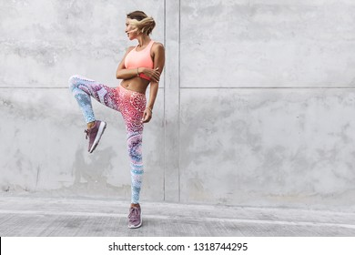 Fitness model in fashion sportswear doing yoga exercise in the city street over gray concrete background. Outdoor sports clothing and shoes, urban style.