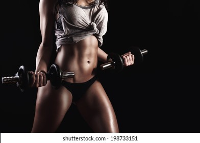 Fitness model in hard training holding steel dumbbells