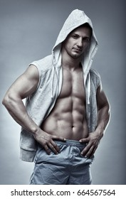 Fitness model with hooded shirt posing on gray background