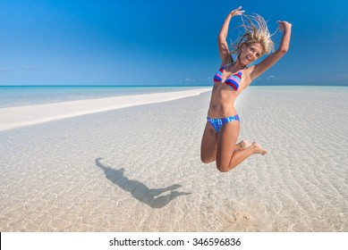A fitness model jumping on pure white beach with rippled sand