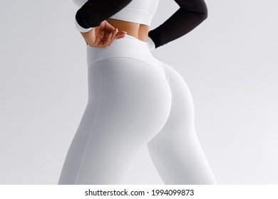 Fitness model in leggings with beautiful buttocks.