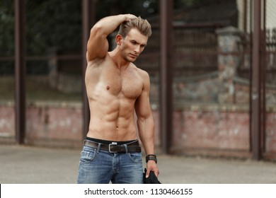 Fitness model man with a hairstyle with a naked body with muscles in a stadium on the street