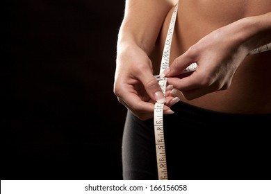 fitness model is measuring her waist on black background