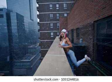 Fitness model morning workout on a hotel rooftop in the rain and snow manhattan, New York