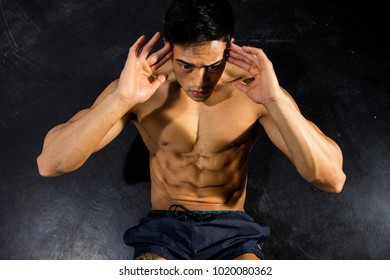 A fitness model performing abdominal crunches. Overhead shot.