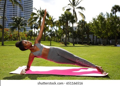Fitness model in a planking pose on a yoga mat in the park