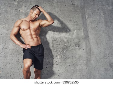 Fitness model portrait copy space, muscular build fit and toned build. Relaxing after workout. no shirt. Room for Copy Space