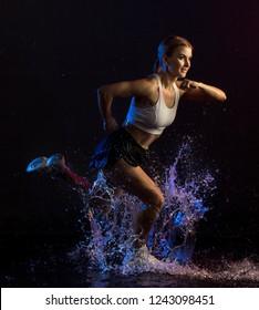 Fitness model running in the dark in water splash