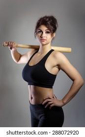 Fitness model shot in the studio holding a baseball bat