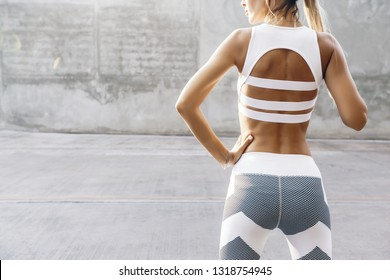 Fitness model in sportswear posing on the city street over gray concrete background. Outdoor sports clothing, urban style.