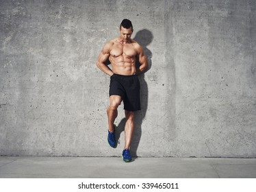 Fitness model standing against grey background, no shirt showing abdominal muscles, room for copy space, fitness concept advertising