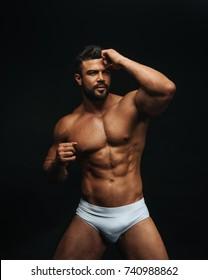 Fitness model in white underwear on black background