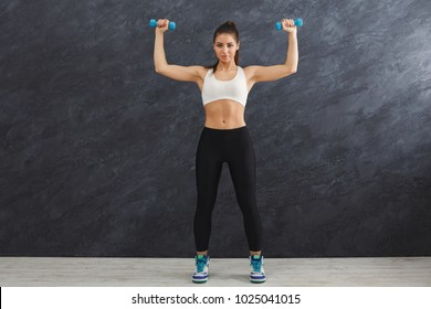 Fitness model woman with dumbbells on grey studio background. Young girl in fitwear with sport equipment. Bodybuilding, healthy lifestyle concept