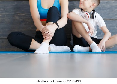 Fitness mother with her 9 years old son. Sports mom with kid relaxing after morning work-out at home. Mum and child do the exercises together, healthy family lifestyle concept