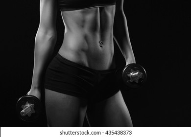 Fitness motivation. Part of fitness body on a black background. Perfect female sports figure. Fitness woman posing in the studio. Fitness photo shoot in the studio. Fitness bikini