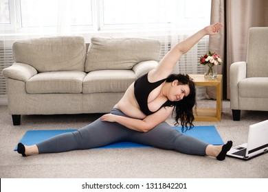 fitness, online personal trainer, home training, technology and diet. overweight woman doing stretching exercises sitting on a fitness mat at home, using laptop