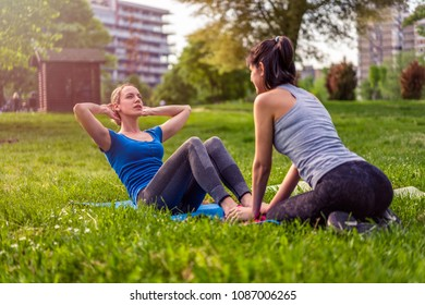 Fitness outdoors. Two beautiful women doing exercises in the park.