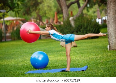 Fitness outdoors - woman stretching with fit ball at pilates workout in park. Sport girl  hold fitball on green grass. Female sport instructor hold yoga exercise ball outdoor in morning - yoga workout