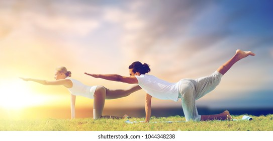fitness and people concept - couple making yoga balancing table pose outdoors over sea background