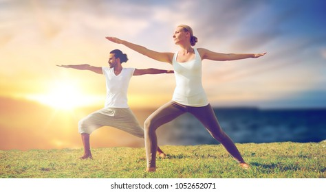 fitness and people concept - couple making yoga warrior pose outdoors over sea background