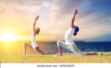 fitness and people concept - couple making yoga low lunge pose outdoors over sea background