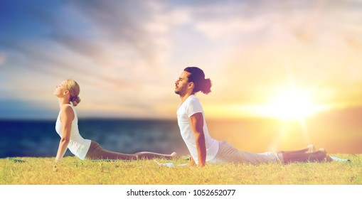 fitness and people concept - couple making yoga cobra pose outdoors over sea background