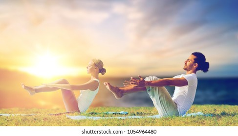 fitness and people concept - couple making yoga half-boat pose outdoors over sea background