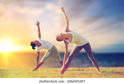fitness and people concept - couple making yoga triangle pose outdoors over sea background