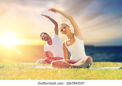 fitness and people concept - couple making yoga exercises on mats outdoors over sea background