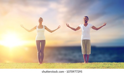 fitness and people concept - couple making yoga exercises outdoors over sea background