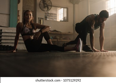 Fitness people doing stretching exercise at gym. Young woman warming up with fitness trainer at gym.