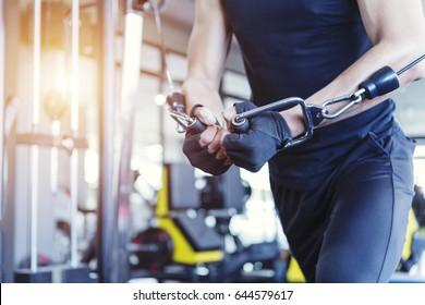 Fitness people execute exercise with exercise-machine Cable crossover in gym.
