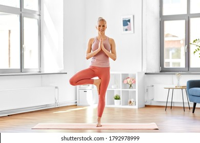 fitness, people and healthy lifestyle concept - happy smiling young woman doing yoga in tree pose at home