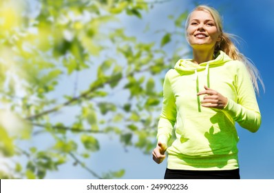 fitness, people and healthy lifestyle concept - happy young female runner jogging outdoors