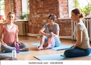 fitness, people and healthy lifestyle concept - group of women in yoga class resting on mats at studio