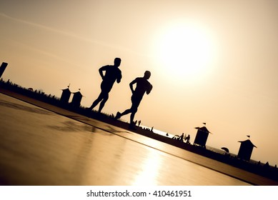 Fitness people running at the beach into the sunset.
