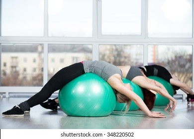 Fitness practice, group of three happy smiling beautiful fit young females working out in sports club, doing backbend exercise on green Swiss balls in class, full length