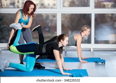 Fitness practice, group of two beautiful fit young females working out in sports club, doing kneeling kickbacks, exercise for lower back, hips and buttocks with instructor in class, full length