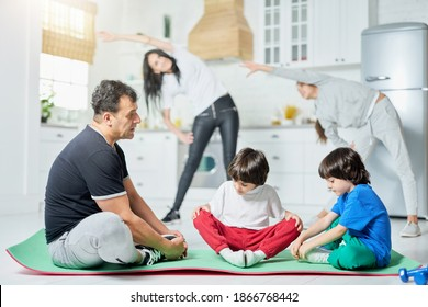 Fitness routine. Full length shot of two little boys sitting on a mat with father while their mom and sister exercising in the background