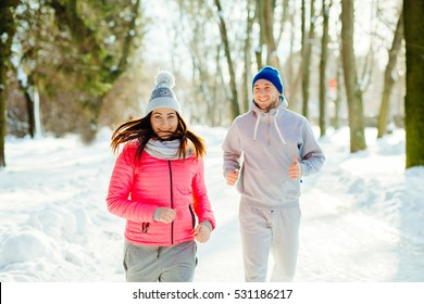 Fitness runner couple working out together outside smiling happy. Health, sport, people and lifestyle concept.