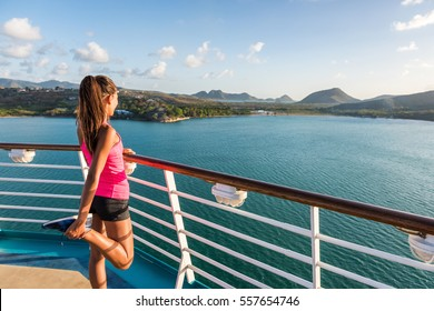 Fitness runner training stretching leg warm-up stretches before running on tracks of cruise ship boat. Woman enjoying view from deck of port of call Castries in St Lucia.